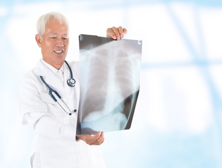 Asian senior doctor checking on x-ray image inside hospital room photo