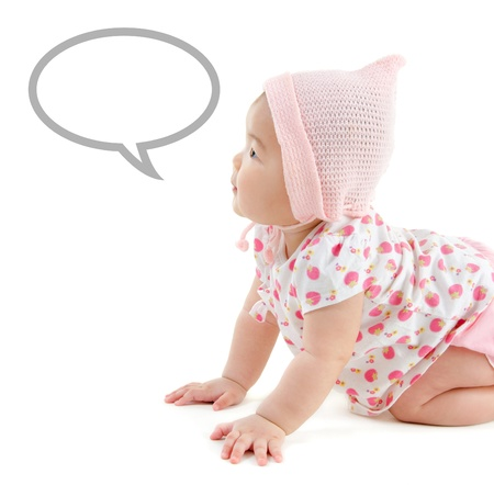 Six months old East Asian baby girl with announcement talk bubble crawling on white background photo