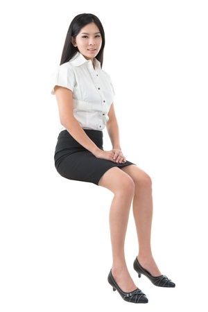Full body young Asian woman sitting on transparent block over white background photo