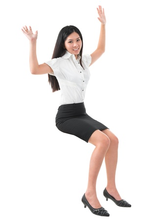 Full body arms raised young Asian woman sitting on invisible chair over white background photo