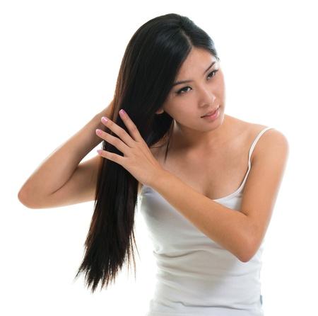 comb hair: La cura dei capelli. Giovane ragazza asiatica che pettina i capelli con il dito isolato su sfondo bianco
