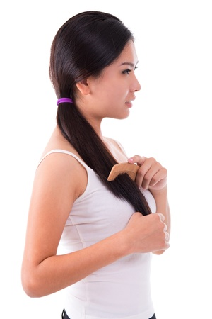 Side view young Asian girl combing hair over white background Stock Photo - 17500986