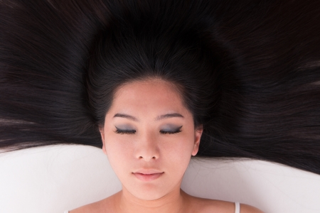 Close up beautiful young Asian girl lying on white with scatter hair Stock Photo - 17500994