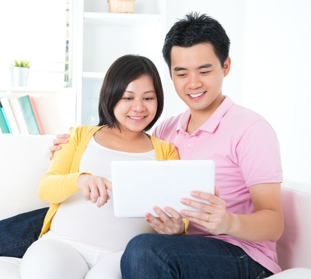 Asian couple. Husband and 8 months pregnant wife using tablet computer sitting on sofa at home photo