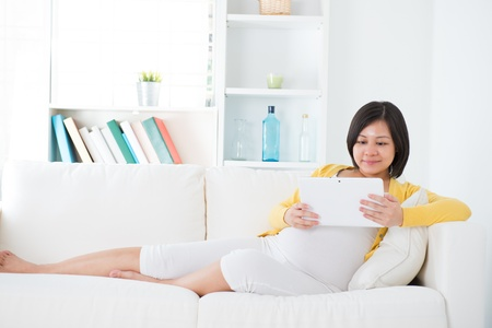 Beautiful Asian  pregnant woman using tablet computer sitting on sofa at home photo