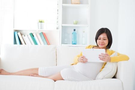 usando computadora: Hermosa mujer asi�tica embarazada utilizando equipo Tablet PC que se sienta en el sof� en casa