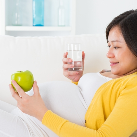 Maternal nutrition. Asian pregnant woman  healthy lifestyle, holding fruit and water glass sitting on sofa at home. photo