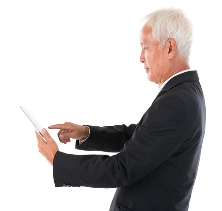 company profile: Side view senior adult Asian Chinese boss using tablet computer standing over white background