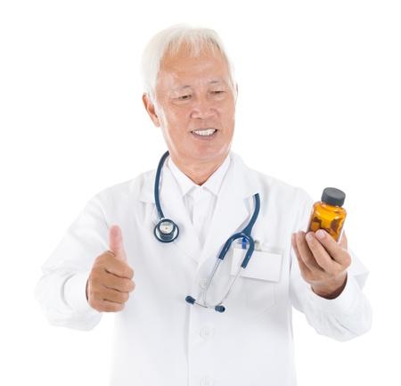 Asian senior medical doctor holding a bottle of pills, thumb up isolated white background photo
