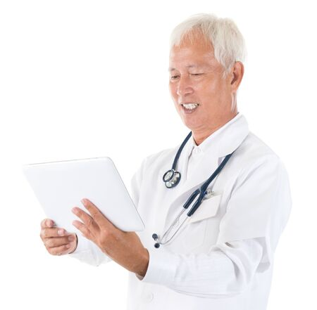 Senior adult Asian specialist medical doctor using tablet computer isolated on white photo