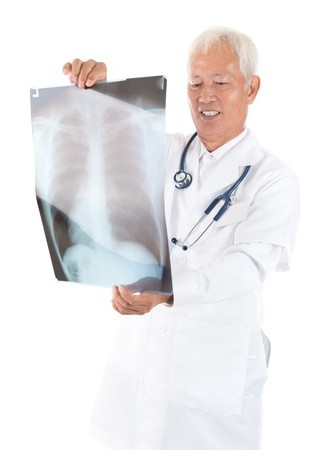 Senior adult Asian medical doctor checking on x-ray image standing isolated white background photo