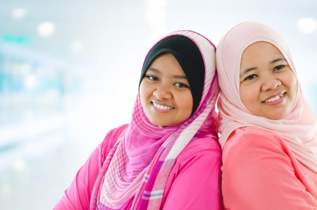 Happy Muslim women standing inside house. Two Southeast Asian girls smiling. photo