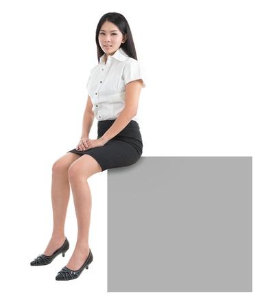 mujer sentada: Chica bastante asiática que se sienta en gran cartel en blanco cartel cartelera con copia espacio. Sonrisa asiática joven modelo chino. Aislado sobre fondo blanco Foto de archivo