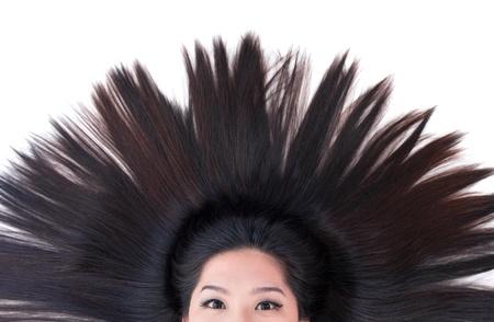 plan éloigné: Belle jeune fille asiatique couché sur le blanc avec les cheveux de dispersion