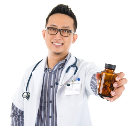 Southeast Asian medical doctor holding a bottle of pills, smiling isolated white background photo