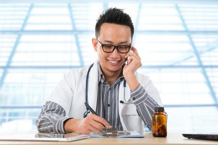 llamando: Jóvenes del Sudeste Asiático médico escribe una nota mientras llama por teléfono, sentado frente a un escritorio dentro del hospital. Foto de archivo