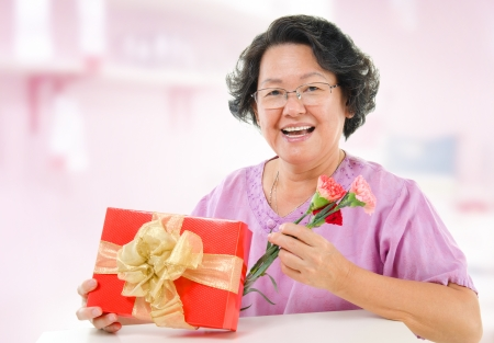 Happy mothers day concept. Asian senior mother showing a gift and carnation flowers at home. photo