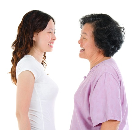 ageing: Ageing concept. Asian senior mother and adult daughter face to face, profile side view smiling isolated on white background. Stock Photo