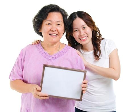 the offspring: Los padres y los hijos adultos de Asia con un cartel en blanco sonriente, aislado sobre fondo blanco Foto de archivo