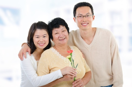 offsprings: Asian family at home. Adult offsprings giving carnation flowers to senior mother. Stock Photo