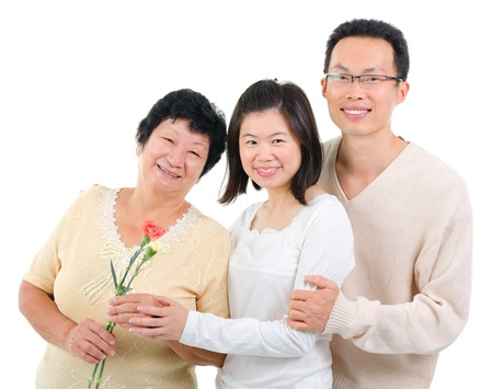 Asian adult offsprings giving carnation flower to senior parent on mother's day. photo