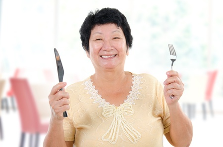 Happy Asian senior mother ready for her Mothers day meal, holding fork and knife inside restaurant. photo