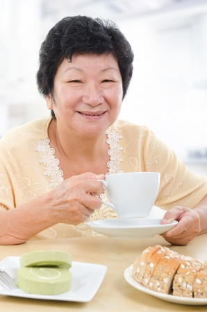 Happy Asian senior woman having breakfast at home photo