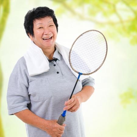 亞洲高級女健康的生活方式。快樂的亞洲祖父母控股羽毛球拍