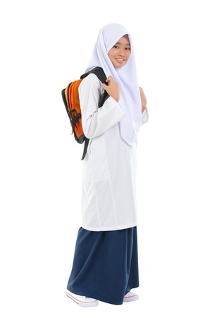 Fullbody Southeast Asian teen in  school uniform with school bag standing over white background photo