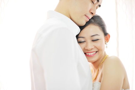 Asian Chinese wedding couple in love. Romantic groom and bride dancing in their wedding day photo