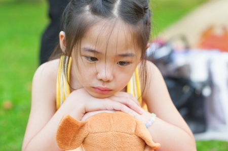 Outdoor upset Asian child. Little girl showing her unhappy face. photo
