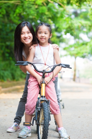 Asian parent and child riding a bike Stock Photo