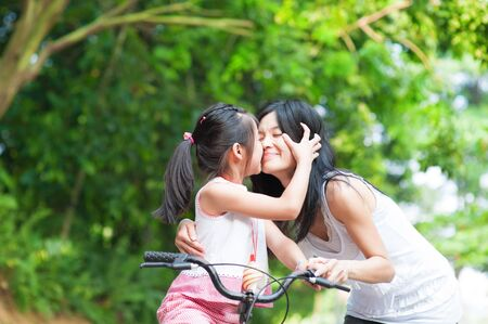 asian family outdoor: Asian child kissing her mother. Asian family having fun outdoor, biking outdoor.
