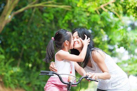 asian child: Asian child kissing her mother. Asian family having fun outdoor, biking outdoor.