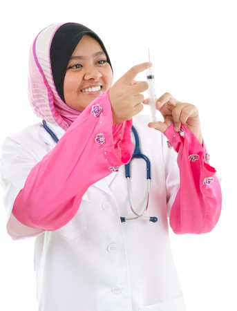 Muslim female medical doctor filling the syringe getting ready for a medical procedure, isolated on white background photo