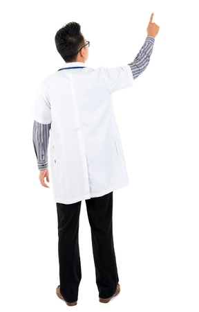 Full body rear view of Asian medical doctor pointing at blank space standing isolated on white background