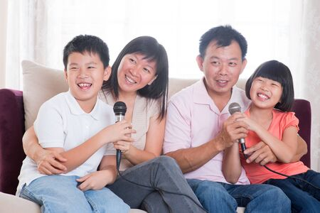 happy asian family: Family at home. Portrait of a happy Asian family singing karaoke through microphone in the living room Stock Photo