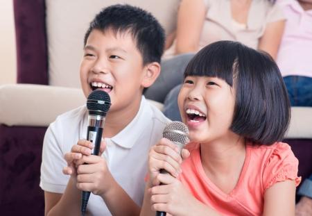 cantando: Familia en el hogar. Retrato de un ni�os felices cantando karaoke de Asia a trav�s del micr�fono en la sala de estar