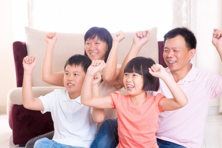 Asian family at home. Portrait of happy parents and children playing game arms raised together at home. photo