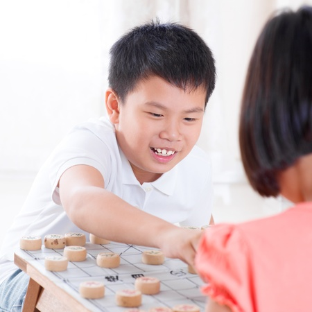 Asian children playing Chinese chess at home. photo