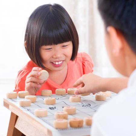 Asian family at home. Asian children playing Chinese chess at home. photo