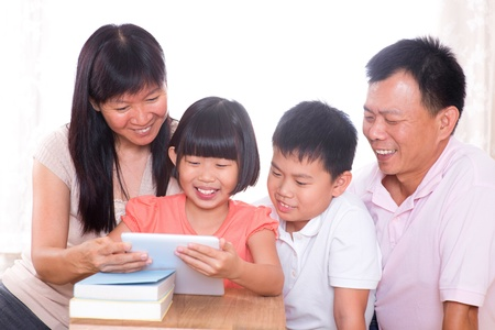 Asian family at home. Parents and children using digital tablet computer together. photo