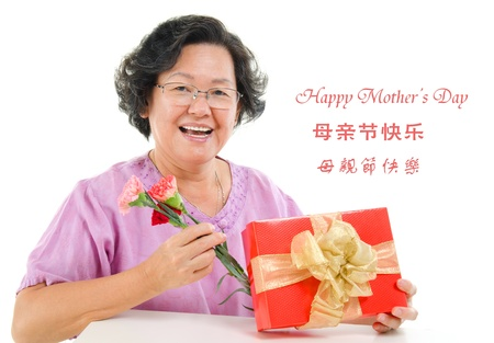 Happy mother's day concept. Asian senior mother showing a gift and carnation isolated on white background. photo