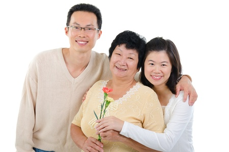 Asian family celebrates Mothers Day. Adult offspring giving carnation flowers to senior mother isolated on white. photo