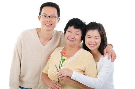 the offspring: Familia asi�tica celebra el D�a de las Madres. Hijo adulto que da las flores de clavel a la madre de altos aislados sobre fondo blanco.