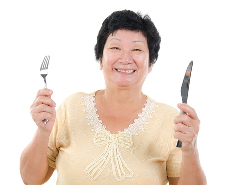holding a knife: Happy Asian senior mother ready for her Mothers day meal, holding fork and knife isolated on white.
