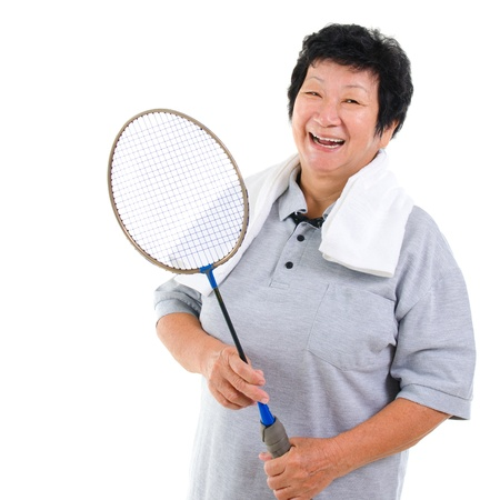 Asian senior woman healthy lifestyle. Happy Asian grandparent holding badminton racket isolated on white. photo