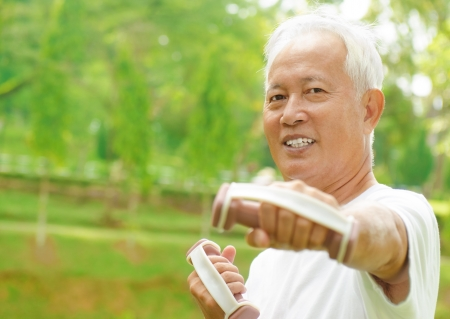 citizen: Asian senior man healthy lifestyle. Happy Asian grandparent playing sport at outdoor green park.