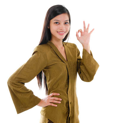 Southeast Asian Muslim female in traditional kebaya with long black hair gestures okay hand sign with great smile standing isolated on white background. photo