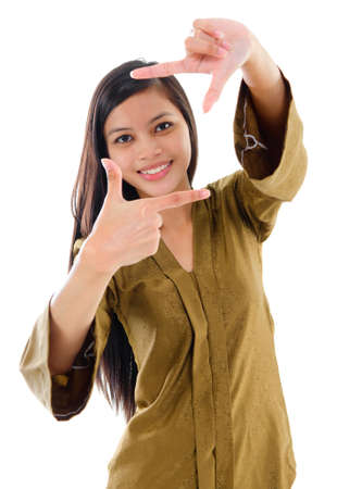 Smiling Southeast Asian Muslim female in traditional kebaya with long black hair making a frame by fingers standing isolated on white background. Stock Photo - 18209060